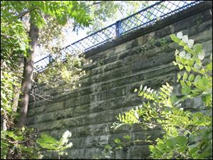 A massive limestone wall from the canal era supports the roadway in the area 400 block of St. Clair Street. The blue guardrail along top of the wall can be seen across the street from the Toledo Main Post Office.
