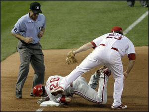 Philadelphia Phillies' Chase Utley (26) is tagged out at third by St. Louis Cardinals third baseman David Freese (23) as third base umpire Chris Guccione looks on during the sixth inning of Game 4 of baseball's National League division series on Wednesday, Oct. 5, 2011, in St. Louis.