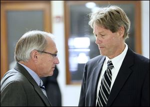 Former Toledo Fire Chief Mike Wolever, left, talks to his son's attorney, George Gerken, after Wednesday's hearing.