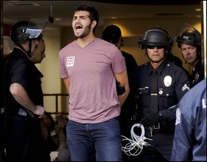 One of several demonstrators is taken into custody by police after refusing to leave a Bank of America branch in downtown Los Angeles, Thursday. The arrests Thursday afternoon came at the end of a demonstration that moved among high-rises housing t
