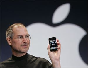 Apple CEO Steve Jobs holds up an Apple iPhone at the MacWorld Conference in San Francisco in this Jan. 9, 2007, file photo.