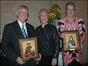 Sylvania Mayor Craig Stough, recipient of the St. Francis Award, Sister Diana Lynn Eckel, congregational minister for the Sisters of St. Francis of Sylvania, and Gayle Lampkowski, chief financial officer for the Sylvania Franciscans and recipient of the St. Clare Award, stand with their icons in honor of St. Francis of Assisi, the founder of the Franciscan Order, and St. Clare, a follower of Francis and founder of the Poor Sisters of San Damiano.