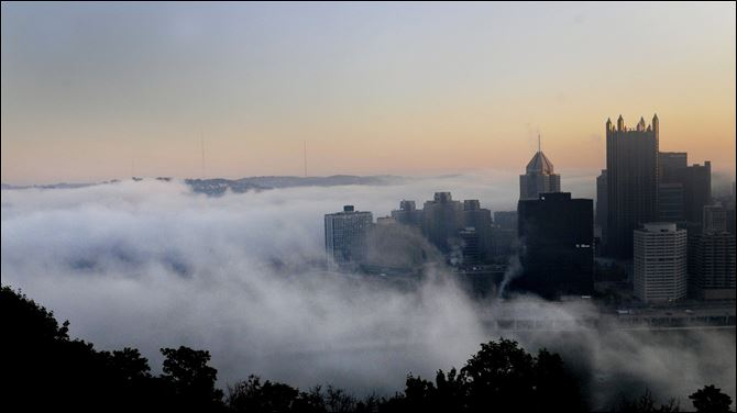 Fog prepares to roll over the Golden Triangle of Pittsburgh at sunrise, Friday .
