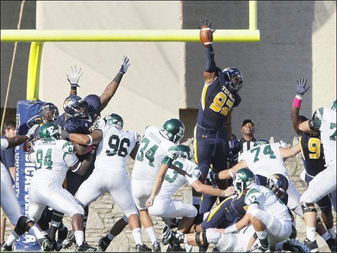 Danny Farr, 92, blocks a PAT attempt for toledo University of Toledo player Danny Farr, 92, blocks a PAT attempt by Eastern Michigan University kicker Kody Fulkerson during the second quarter at the Glass Bowl, Saturday.