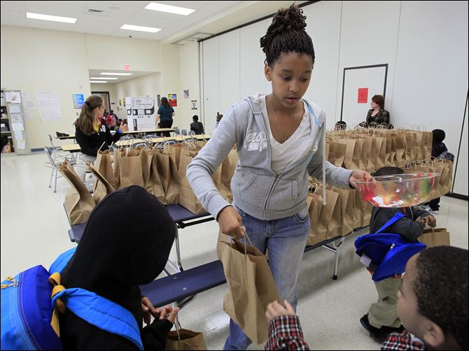 Toledo area students receiving weekend care packages Eighth-grader Kya Mabrey hands out bags of food to kindergartners as Spring Elementary students receive a brown bag full of food for the weekend, Friday.