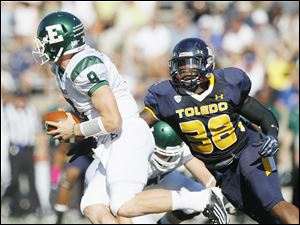 University of Toledo player Robert Bell, 38, sacks Eastern Michigan University quarterback Alex Gillett, 8, during the second quarter.