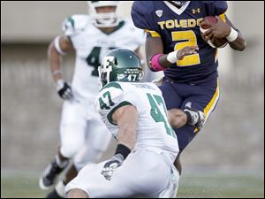University of Toledo quarterback Terrance Owens, 2, cuts back against Eastern Michigan University defender Justin Cudworth, 47, during the third quarter.