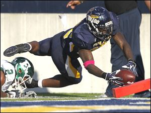 University of Toledo player David Fluellen, 22, dives for the pylon but is pushed out of bounds at the two yard line by Eastern Michigan University player Latarrius Thomas, 2, during the third quarter.
