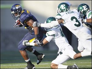 University of Toledo player Kenny Stafford, 7, picks up a first down before being tackled by Eastern Michigan University players Marlon Pollard, 4, and Willie Williams, 3, during the third quarter.