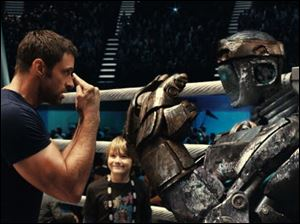 "Hugh Jackman, left, and Dakota Goyo face off in a scene from ""Real Steel."" The film is set in the near-future when robot fighters have replaced humans in the ring. The film debuted at No. 1 with $27.3 million. The ""Real Steel"" added $22.1 million in 19 overseas markets for a worldwide total of $49.4 million."