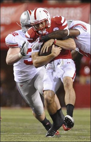 Ohio State's C.J. Barnett, right, sacks Nebraska quarterback Taylor Martinez as Storm Klein (32) moves in.