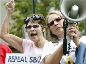 Carol Love, left, and Mary Anthony, right, from Toledo, hold signs and chant slogans with a megaphone.