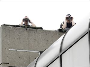Members of the Toledo Police Department are perched on the top floor of a parking garage to monitor the Occupy Toledo event on Levis Square.