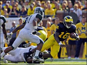 Michigan quarterback Denard Robinson (16) is tripped up on a carry in the second quarter of last year's game. The Wolverines lost 34-17.