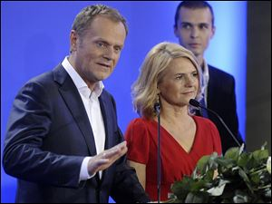 Prime Minister Donald Tusk stands beside his wife Malgorzata, right, as he delivers a speech as the first exit poll have been published during the election party of Tusk's Civic Platform, a centrist and pro-EU party,  in Warsaw.