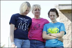 Tanya Zuvers, mother of Andrew, Alexander, and Tanner Skelton, who have been missing since Nov. 27, 2010, is flanked by her daughters Courtney Derby, left, and Brittany Derby as they listen to a song during the prayer vigil in Wakefield Park.