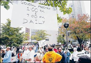 A 'General Assembly' sign hangs above rally participants to announce the times for people to come together in Levis Square in downtown Toledo to show their discontent.