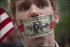 A protester affiliated with the Occupy Wall Street protests stands with a US dollar bill taped over his mouth in Zuccotti Park in New York.