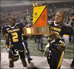 The Peace Pipe Trophy will be permanently housed at the University of Toledo, as they won it in 2010. UT's Taikwon Paige (2) and Archie Donald (42) celebrate the 2010 win at the Glass Bowl with the retired award.