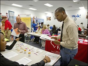 Job seekers attend a career fair at a Goodwiill store Tuesday, Oct. 4, 2011 in Atlanta. The number of people who applied for unemployment benefits rose slightly, a sign that the job market remains weak.