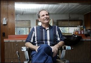 Ron Hurley sits in the chair of his Temperance, Mich., barbershop. He is leaving the trade because of a progressive case of arthritis.