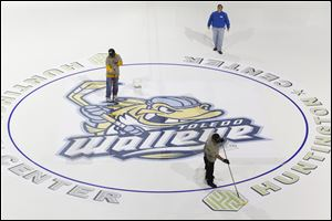 Workers finish putting down the logo at center ice to get the Huntington Center ready for its third season of Walleye Hockey. The arena's capacity is 7,431.