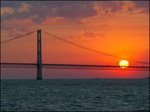 The sun sets over the Mackinac Bridge and the Mackinac Straits as seen from Lake Huron.