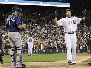 Detroit Tigers' Jhonny Peralta reacts in front of Texas Rangers catcher Yorvit Torrealba after his solo home run in the sixth inning of Game 3 of baseball's American League championship series Tuesday, Oct. 11, 2011, in Detroit.