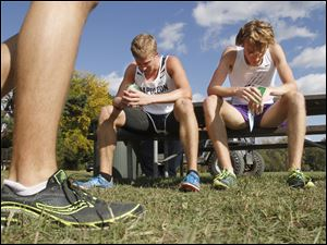 Napoleon's Steve Weaver, left, and Maumee's Willy Fink, right, cool off after the Northern Lakes League cross country championship meet at Pearson Metropark in Oregon, Saturday. Weaver won the race and Fink was second.
