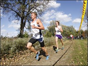Napoleon's Steve Weaver, left, leads Maumee's Willy Fink, right, mid way through the Northern Lakes League cross country championship meet at Pearson Metropark in Oregon, Saturday.