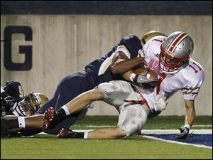 St. John's defenders Evan Yoder and Tony Harper tackle Central's Logan Lorenzen several moments too late to prevent a touchdown during a game on Friday, at University of Toledo's football stadium. Central won 35-14.