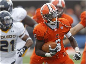 Bowling Green running back Anthon Samuel carries the ball as Toledo's Ross Madison (21) gives chase.