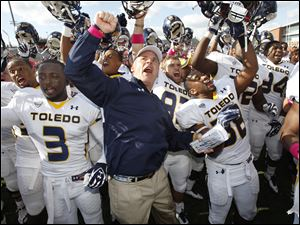 University of Toledo football coach Tim Beckman and his team, including players Desmond Marrow (3) and Robert Bell (38), celebrate after the Rockets beat Bowling Green State University 28-21 to win the Battle of I-75 at Doyt Perry Stadium in Bowling Green.