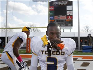 Toledo's Desmond Marrow carries a headless stuffed Falcon in is teeth after the Rockets beat Bowling Green.