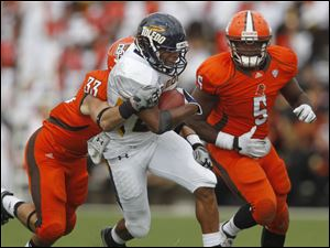 Bowling Green's Aaron Foster tries to stop Toledo's Morgan Williams as Falcons teammate Dwayne Woods (5) also pursues.