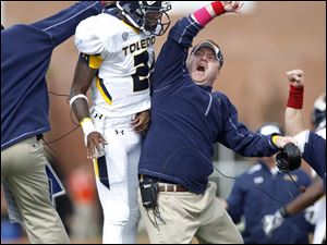 Toledo quarterback Terrance Owens celebrates with tight ends coach Alex Golesh after Toledo scored against Bowling Green in the third quarter .