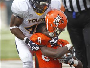 Bowling Green running back Anthon Samuel loses his helmet a while being tackled by Toledo's Terrell Anderson (49).