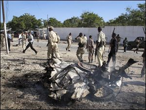Somali government forces attend the scene of a car bomb in Mogadishu, Somalia.