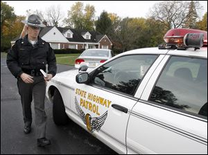 Sgt. Brian Foltz, with the Ohio Highway Patrol, returns to his vehicle after citing a driver for violating school bus traffic laws near the Sylvania Whiteford Elementary School on October 18.