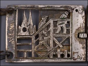 This picture made available by the Auschwitz Museum shows a metal bracelet with images of inmate ordeal found at Auschwitz Nazi death camp after World War II.