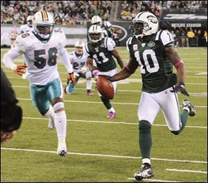 Jets wide receiver Santonio Holmes (10) runs past the Dolphins' Kevin Burnett (56) on his way to a touchdown during the fourth quarter.