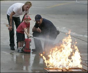 Duane LaHote, left, watches his son, Camron LaHote, 4, of Delta, use a fire extinguisher.
