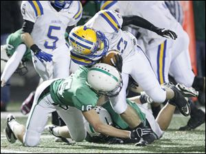 Ottawa Hills player Doug Stockton, 16, tackles Northwood's Evan Perkins, 22, during the second quarter.