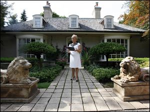 Real estate agent Ronni Keating waits outside a home in Bloomfield Hills, Mich. In the luxury sector, the recession is a memory and prices are rising. But everywhere else, the housing market is still suffering.