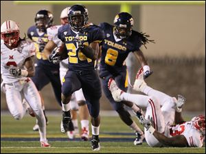 University of Toledo running back Adonis Thomas, 24, breaks away for long run against Miami during the first quarter Saturday,  at the Glass Bowl.