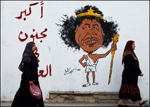 "Libyan women walk past a graffiti reading: ""The greatest Crazy of the World"" in Tripoli, Libya, Friday."