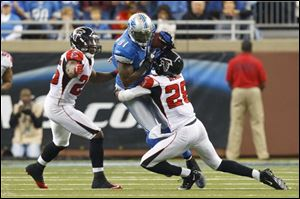 Lions wide receiver Calvin Johnson (81) is tackled by Falcons free safety Thomas DeCoud (28) and defensive back Kelvin Hayden (26) in the second half.