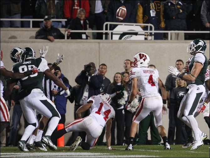 Wisconsin Michigan St Football hail mary pass The ball goes up for grabs and into the arms of Michigan State's Keith Nichol, right, after being tipped on a pass on the final play of an NCAA college football game, Saturday, Oct. 22, 2011, in East Lansing, Mich. Also seen are Wisconsin's Marcus Cromartie, 14, Aaron Henry, 7, and Jared Abbrederis, 4, and Michigan State's Dion Sims, 80, and B.J. Cunningham, left rear.