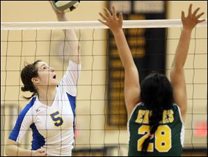 St. Ursula's Katie McKernan (5) spikes the ball against Clay's  Katey McQueary (28) Tuesday.
