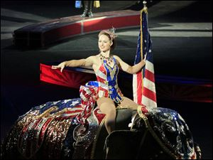 The national anthem is sung ringmaster Brian Crawford Scott as a performer riding an elephant carries the American flag.